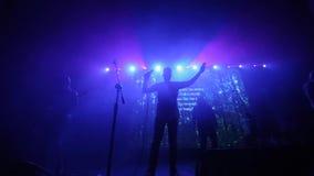 Ein Mann mit zwei hob übergibt oben die Ausführung an einem Konzert an Blaue Leuchte Schattenbilder von sechs Musikern Die Frau,  stock video footage