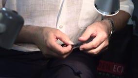Ein Mann näht Kleidung in einer Hand stock video footage