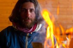 Ein Mann nahe einem Feuer Stockbild