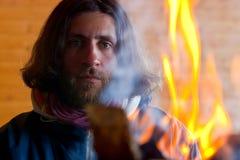 Ein Mann nahe einem Feuer Lizenzfreie Stockfotos