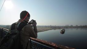 Ein Mann nimmt auf Kamera einen langen Lastkahn, der auf einen Fluss schwimmt stock footage