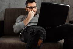 Ein Mann passt ein erwachsenes Video auf einem Laptop beim Sitzen auf der Couch auf Das Konzept der Pornografie, der Bedarf der M lizenzfreie stockfotografie
