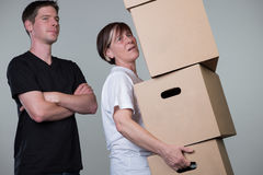 Ein Mann passt gerade auf, während eine Frau schwere cardboxes trägt Lizenzfreies Stockbild