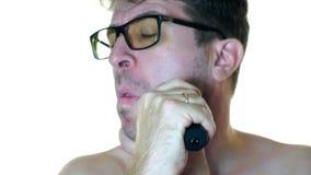 Ein Mann rasiert seinen Elektrorasierer gegen einen weißen Hintergrund Nahaufnahme stock footage
