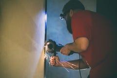 Ein Mann repariert eine T?r im Keller seines Hauses unter Verwendung einer Handschleifenmaschine lizenzfreie stockbilder