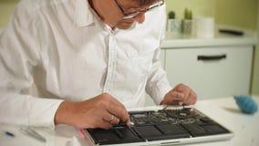 Ein Mann repariert einen Laptop Das Konzept der Computerreparatur Schließen Sie oben vom Mannreparatur-Laptopmotherboard mit a stock video