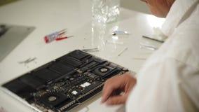 Ein Mann repariert einen Laptop Das Konzept der Computerreparatur Schließen Sie oben vom Mannreparatur-Laptopmotherboard mit a stock video footage