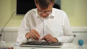 Ein Mann repariert einen Laptop Das Konzept der Computerreparatur Schließen Sie oben vom Mannreparatur-Laptopmotherboard mit a stock footage