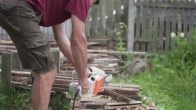 Ein Mann sägt Holz mit einer elektrischen Säge stock video
