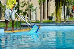 Ein Mann säubert das Pool Stockbild