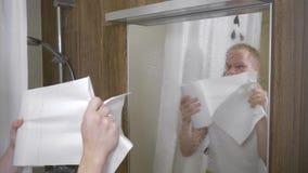 Ein Mann säubert den Spiegel im Badezimmer Ein junger Mann säubert den Badezimmerspiegel mit Papierhandtüchern 4K stock footage