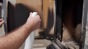 Ein Mann säubert Glas durch einen Kamin vom Ruß stock footage
