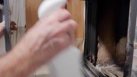 Ein Mann säubert Glas durch einen Kamin vom Ruß stock video