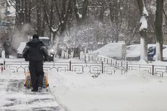 Ein Mann säubert Schnee von den Bürgersteigen mit Schneekanone Stockbilder