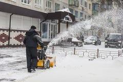 Ein Mann säubert Schnee von den Bürgersteigen mit Schneekanone Lizenzfreie Stockbilder