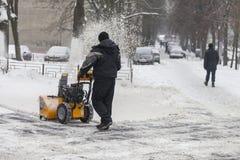 Ein Mann säubert Schnee von den Bürgersteigen mit Schneekanone Stockfotos