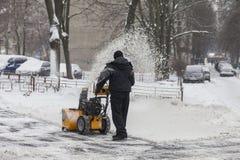Ein Mann säubert Schnee von den Bürgersteigen mit Schneekanone Stockbild