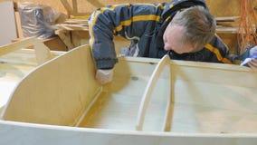 Ein Mann sammelt ein Boot, das vom Holz hergestellt wird Er nimmt an Handarbeit teil stock footage
