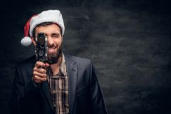 Ein Mann in Sankt-` s Hut hält die alte 8mm Videokamera Stockfoto
