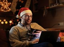 Ein Mann Sankt-` s im Hut neuen Jahres hält eine Katze und das Arbeiten mit Laptop Stockbild