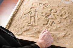 Ein Mann schaut auf gezogenem auf den Sandzahlen Lizenzfreie Stockfotos