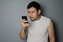 Ein Mann schaut am Handy lizenzfreie stockfotografie