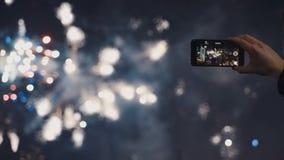 Ein Mann schießt ein selfie Video eines festlichen pyrotechnischen Zeigunges in einer Nachtstadt Stockfotografie