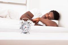 Ein Mann schläft mit einem Wecker Stockfotografie