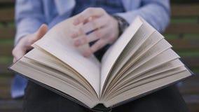Ein Mann schlägt eine Seite beim einen Buchabschluß oben lesen leicht stock video footage