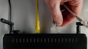 Ein Mann schließt das Ethernet-Kabel an die WAN- und LAN-Häfen des WiFi-Routers an nahaufnahme stock footage