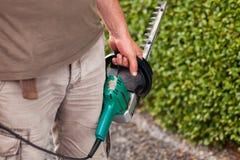 Ein Mann schneidet die Hecke durch die Heckenschere Lizenzfreie Stockfotos
