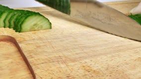 Ein Mann schneidet Gurken für Salat Chefcook hacken Scheiben-Gurke stock footage