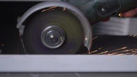 Ein Mann schneidet ein Metall mit einem Bulgaren stock video