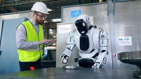 Ein Mann schreibt auf einer Tablette, während ein Cyborg mit einem Fabrikdetail arbeitet stock video footage