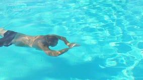 Ein Mann schwimmt unter Wasser in Pool stock video