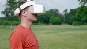 Ein Mann setzt einen VR-Kopfhörer auf seinen Kopf in den Park ein stock footage
