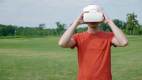 Ein Mann setzt einen VR-Kopfhörer auf seinen Kopf in einen Park ein stock video footage