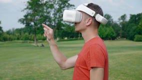 Ein Mann setzt einen VR-Kopfhörer auf seinen Kopf in einen Park und in Anfänge mit ihm ein stock video