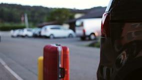 Ein Mann setzt helle Koffer in das Auto ein touristen stock video