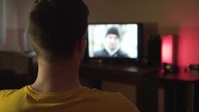 Ein Mann sieht im Wohnzimmer spät nachts fern Ein Mann sitzt im Rahmen von seinem zurück durch das Licht einer Lampe stock video footage