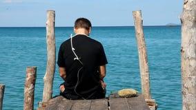 Ein Mann sitzt auf einem Pier mit einer Schleife stock video footage