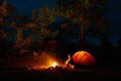 Ein Mann sitzt durch das Feuer nahe einem Zelt auf dem Ufer vom Baikalsee Stockbild