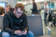 Ein Mann sitzt in einem Flughafenabfahrtanschluß, der seine geliebten auf seinen folgenden Flug zu Hause wartend simst stockbilder