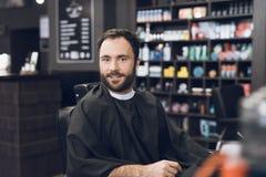 Ein Mann sitzt in einem Friseur ` s Stuhl in einem Mann ` s Friseursalon, wohin er kam, sein Haar zu schneiden Stockbilder