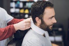 Ein Mann sitzt in einem Friseur ` s Stuhl in einem Mann ` s Friseursalon, wohin er kam, sein Haar zu schneiden Lizenzfreie Stockfotografie