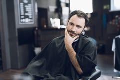 Ein Mann sitzt in einem Friseur ` s Stuhl in einem Mann ` s Friseursalon, wohin er kam, sein Haar zu schneiden Stockfotografie