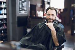 Ein Mann sitzt in einem Friseur ` s Stuhl in einem Mann ` s Friseursalon, wohin er kam, sein Haar zu schneiden Lizenzfreie Stockbilder
