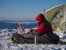 Ein Mann sitzt in einem Schlafsack nahe dem Zelt und den Schneeschuhen stockfoto
