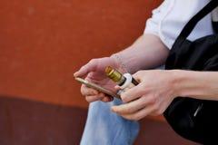 Ein Mann sitzt mit einem Telefon und dem Vaping stockbild