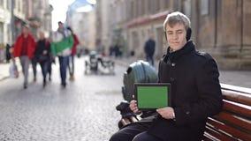 Ein Mann sitzt mit Tablette stock video